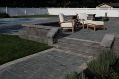 Multi-level patio with built-in seating wall. Built using @cambridgepavers.