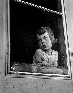 Erika Stone - Child behind screen door. Canada, 1956. °. If you look closely, you can see eyes at the left side of her head. :(
