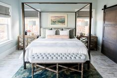 In this master bedroom, modern farmhouse meets upscale sophistication. Using bold elements like the metal frame canopy bed in conjunction with unexpected light, airy pastels for the color palette, designer Mollie Openshaw was able to create a space that makes a statement, but is also restful and serene.