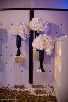 Tufted white walls with black vases and white orchids
