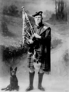 Dog and bagpiper, Bowen, 1921. Studio portrait of a bagpiper in traditional highland dress.
