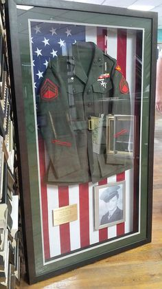 WWII Military Jacket with Plaque and Picture Shadowboxed with an American Flag background. Bill's Custom Framing