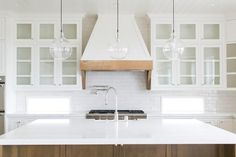 Three glass pendants hang above a coffee stained center island finished with a white marble countertop and a farmhouse sink with a polished nickel gooseneck faucet facing a stainless steel oven range positioned beneath a white french kitchen hood accented with a rustic wood trim and fixed on white subway tiles between glass front cabinets mounted over small rectangular windows placed above white lower cabinets.