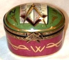 "Here is a beautifully made hand-painted oval French porcelain snuff / pill box with a super bronze hinge and Masonic tools clasp.   The porcelain top depicts the Holy Bible with the Square & Compasses in shades of green, ivory and trimmed in gold.  My favorite part of this box is that under the front clasp is a hand-painted ""W"" denoting ""west"" and the under the back hinge is a hand-painted ""E"" denoting ""east"" symbolic of traveling from ""west to east."""