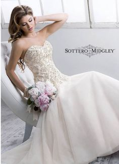 Quincy Maggie Sottero # 4SN805LU. This gown has a beaded lace bodice and a tulle skirt. It is finished off with a corset back closure.