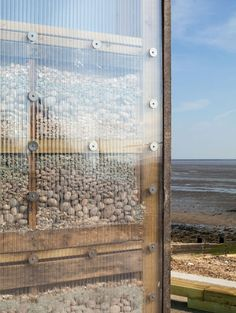 Stones and shells from the seashore fill the walls of these eight contemporary British beach huts.