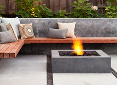 Wood bench wraps around a low concrete fire pit