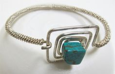 Sterling Silver Wire Art Bracelet: This 7 inch bracelet is created with sterling silver-filled wire and wrapped with twisted silver-filled wire.  A turquoise fan shaped gemstone bead makes a beautiful accent<br /> by Sandra Light