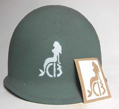 Very rare helmet stencil for the famous 'SeeBees' - it features a mermaid and the text 'CB' which comes from the term Construction Battalions. This stencil comes from a very early war helmet before the stencil changed to a 'Fighting Bee'.  The need for a militarized Naval Construction Force to build advance bases in the war zone was evident when under international law civilian engineers could be executed if they resisted military forces. The SeeBees were thus formed.   www.warhats.com