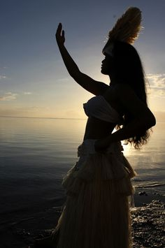 Polynesian dancer dressed in a traditional Ote'a costume with the Sunset in Tahiti