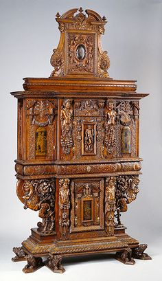 Getty Museum - Cabinet by an unknown maker, French 1580 with minor additions from the late 1850s. Carved walnut and oak with painted panels, linen and silk lining. 10 ft. 1 1/8 in. high. Details below: drawer pull, grisaille painting on the right door, and a carved figure.