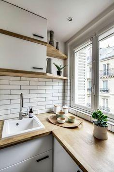 amenagement petite cuisine, crédence en briques blanches, meubles blancs avec poignées noires, plan de travail des meubles en surface imitation bois clair, lavabo blanc, étagères en angle en bois clair, crédence en briques blanches