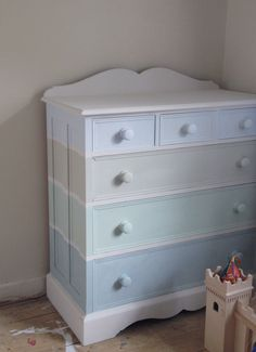 My childhood pine chest of drawers hand painted with chalky beachhut stripes in Small Boy's favourite blues and greens. It'll look lovely topped with his fish tank, opposite the vintage photo wall and on the glossy white floor once it's painted.  His seasidey room is slowly getting there!