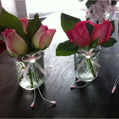 DIY Centerpieces for Baby Shower: Repurposed mason jars, ribbon and pacifier gift ties at neck, flowers from Costco