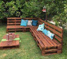 un canapé en palette, type banc coussins décoratifs en bleu et blanc, table basse, salon de jardin en palette