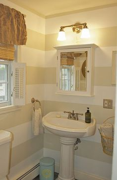 Small Bathroom Makeover - Love the striped walls.  Bamboo shades, cafe plantation shutters and a valance on the window!