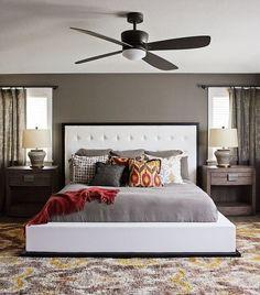 un ventilateur élégant au-dessus du lit en blanc et gris dans la chambre à coucher
