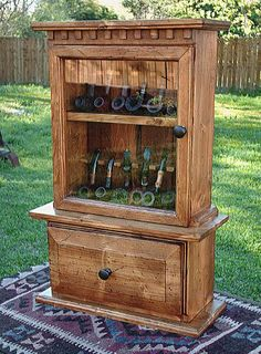 """Hargrove Estate  27.5"""" h x 18"""" w x 8"""" deep Holds 12 pipes.  Finished in an antique distressed pine, this rack would proudly display your prized pipes. It has a drop down cabinet door exposing a storage compartment, and a glass front door with antique bronze knobs. Handmade dental trim on the top gives this an air of elegance, and felt lined pipe rests will keep your collection cozy. – M  $350"""