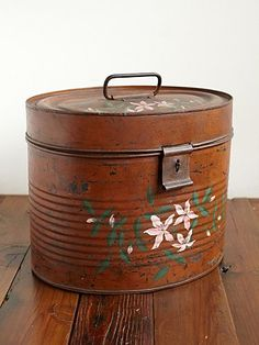 vintage 1920's tin hat box with painted floral detailing. Clasp closure with handle