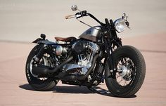 "Built by Lluís Ibañez Casabon of L.A. Motorcycles in Barcelona. Based on a 2006-model Sportster 883 Low. Retro bobber flavour, custom tank from Salinas Boys, pre-War Harley VL style springer forks, matching Phantom headlight. Rear suspension is more modern, with 11"" shocks from Progressive, nestling alongside a ""Flat Bob"" rear fender and a replica pre-War taillight. Avon Speedmaster tires on 16"" rims complete the look. With only the grips and leather seat providing a touch of colour."