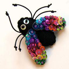 Die bezaubernde Brosche in Form von der bunten Fliege, aus dem Filz und den kunstvoll angenähten Flittern ausgeführt, er wird die einzigartige Ergänzu