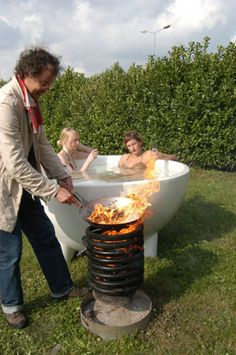 It's a Dutchtub. The water is heated by burning wood in the coiled heating element and you can hop in to a nice toasty outdoor bath. I want to incorporate one of these into the fire pit to heat the pool.
