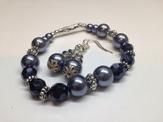 """Bracelet et BO #019 ($20) Bracelet et de boucles d'oreille fait de perle de verre grise, de swarovski et de bille en métal anti-ternissement monté sur un élastique.  Bracelet grandeur 8 pouces (20 cm)  -Perle de verre grise de 10 mm  -Swarovski de 8 mm -Bille de métal anti-ternissement   Boucles d""""oreille:  -Perle de verre grise de 10 mm -Billle de métal anti-ternissement Fait a la main"""