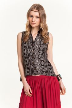 A roomy v-neck buttoned blouse designed with a rippling high/low or arched hem cropped above the hips.