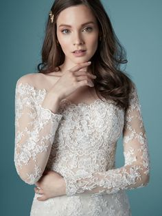 The sartorial triple-threat: sexy, chic, and timeless, á la this off-the-shoulder sheath wedding dress in flirty lace and elegant illusion.