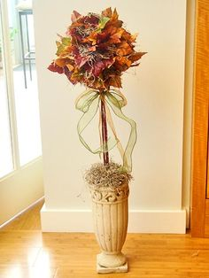 "Fall Leaf Topiary  This elegant topiary is so simple to make. Simply hot-glue your favorite fall leaves and some greenery to a foam ball, then ""plant"" it in a beautiful container."