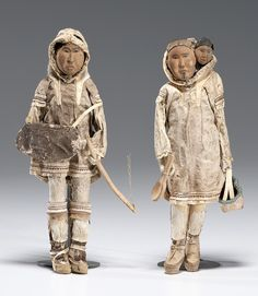 Wood-carved Eskimo Dolls wearing traditional seal hide clothing.
