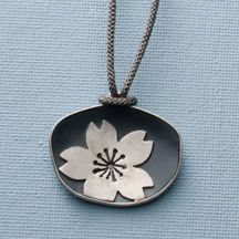 A single, large silver sakura cherry blossom flower contrasts with an organically shaped, concave, rustic oval disc, resulting in a pendant that is simply stunning. A mix of oxidized and non-oxidized sterling silver, pendant is 1 1/2 w x 1 1/4 l and hangs from a hand-woven and hand-dyed, adjustable, charcoal gray 29 cord. Made in the USA by Kristina Kada of Satomi Studios.