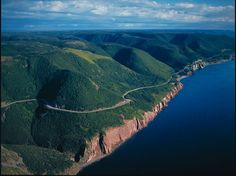 An aerial view of the park from the Gulf. The Cabot Trail winds around the edge of the plateau. The highlands plateau, with its steep cliffs and fantastic ocean scenery, is the most striking feature of Cape Breton Highlands National Park. Cabot Trail, Nova Scotia, Westminster, Provence, Places To Travel, Places To Go, Camping Places, Ontario, Alaska