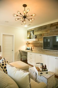 Industrial light fixture and reclaimed wood accent wall makes this TV loft pop with comfort and sophistication in our Designer Showcase Cherry Laurel model home! We love the functionality of the cabinets and built in desk too!