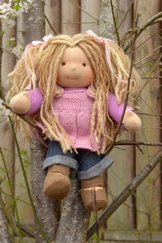 This is Jemma.  She has sunkissed skin, long multi tonal blonde hair made with mohair, mini dreads and wool yarns. She has brown eyes and is wearing the pictured outfit including a hand knit woolen jumper with two wooden buttons, underpants and wool felt shoes