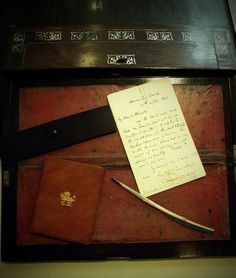 Charles Dickens' travel desk, inlaid in pearl is shown.  His quill pen, manuscripts, and small album are included in the collections, which is housed in the Albert and Shirley Small Special Collections Library at the University of Virginia.