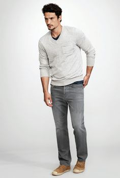 True Religion Brand Jeans men's grey jeans paired with a v-neck sweater over v-neck tee. Shop for grey jeans at PremiumDenimJeans.com