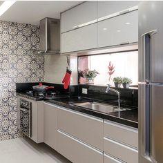 Cozinha com bancada preta e armários superiores em vidro + fendi. Detalhe para os azulejos revestindo a parede lateral. Projeto | Ponto 5…