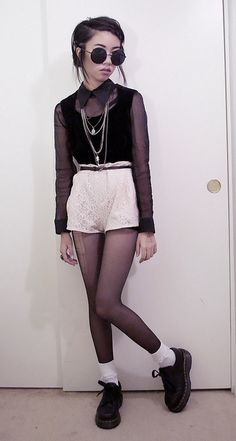 round sunglasses, chains, sheer blouse, there's something missing/not right but it looks cool i think