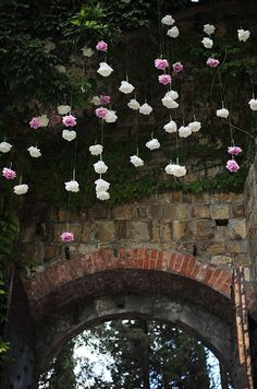 Hanging white and purple roses create an ethereal feel overhead.