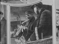 """Two street peddlers together with a basket of wares: """"A noisemaker. A noisemaker for Purim."""" """"Just a lot of noise. Rattles for the Purim celebration."""" (Yiddish and English captions. From a photo essay in the """"Forward"""": """"The Latest From The Old Country."""")"""