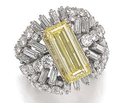 Step-cut yellow diamond weighing 5.00 carats, within a cluster of brilliant-cut and baguette diamonds. Sotheby's. Geneva, May 2014.