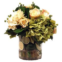 Silk hydrangea arrangement with faux roses and limes in a clear vase.   Product: Faux floral arrangementConstruction...