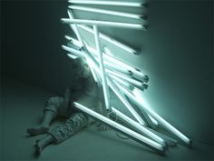 Bernardí Roig is an artist from Mallorca, Spain who explores concepts of loneliness, death, and immortality with his surreal light sculptures. Roig frequently uses a portly white figure made of polyester resin who is seen interacting with fluorescent lights, sometimes staring at it with a childlike curiosity, while in other installations appearing to be violently blinded