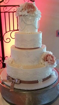 Four-tier vintage lace wedding cake with rose peonies, satin ribbon, and pearls. Buttercream icing.