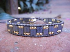 Wrap bracelet with Miyuki Tila beads and gold vermeil nuggets on natural gray leather.