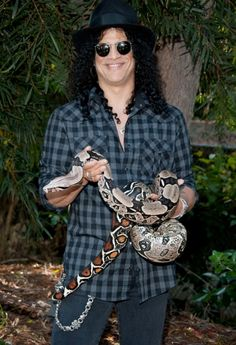 Slash poses with Jacob, his Columbia Red Tail boa constrictor