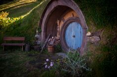 little hobbit home with round blue wooden door, wood bench and flower garden