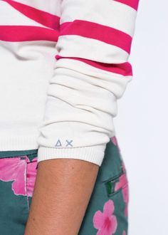 Lines, colours and unexpected cuts: pair a refined knitted sweater in white, with pink stripes and buttons on one shoulder, with a pair of dark green chinos with a floral print.  SUN68 Woman SS15 #SUN68 #SS15 #woman #sweater #bermuda
