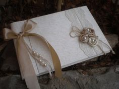This is a very elegant guest book! Its all covered with ivory silk fabric. On the left the album is tided with a satin ribbon.On the right three wonderful satin flowers are lying on two rows of a beautiful ivory lace. The pearls complete the effect. Suitable for an elegant, romantic